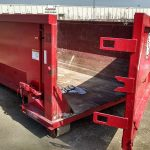 Side photo of red 20 yard dumpster rental with door for rent