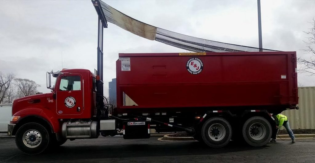 Red truck unloading roll off Container rental