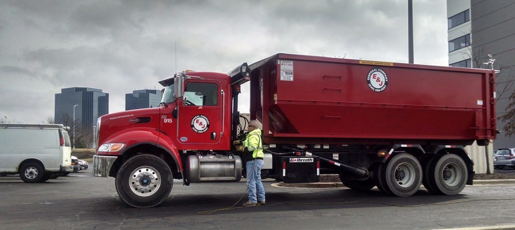 Elgin dumpster rental company unloading roll-off container